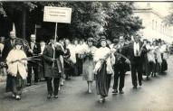 """Vecpiebalgas novada koris Dziesmusvētku gājienā. Priekšplānā ar ziediem rokās 1. no labās Inese Zārdiņa, 2. vīrietis aiz viņas ar ziediem rokās kolhoza """"Alauksts"""" priekšsēdētājs Andrejs Jurciņš"""