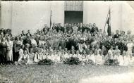 Dziesmusvētku atskaņas pasākumu dalībnieki Vecpiebalgā, 1930.gada 24.jūnijā pie Vecpiebalgas baznīcas durvīm. Centrā mācītājs A. Trucs.