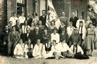Vecpiebalgas Labdarības biedrības koris ar karogu pie biedrības ēkas 20.gs. 20.gadi. 2.rindā 5. no kreisās skolotājs un diriģents Jēkabs Kornets, 6. Eglītis 7.Pētersons 8. Pēteris Zirnis.